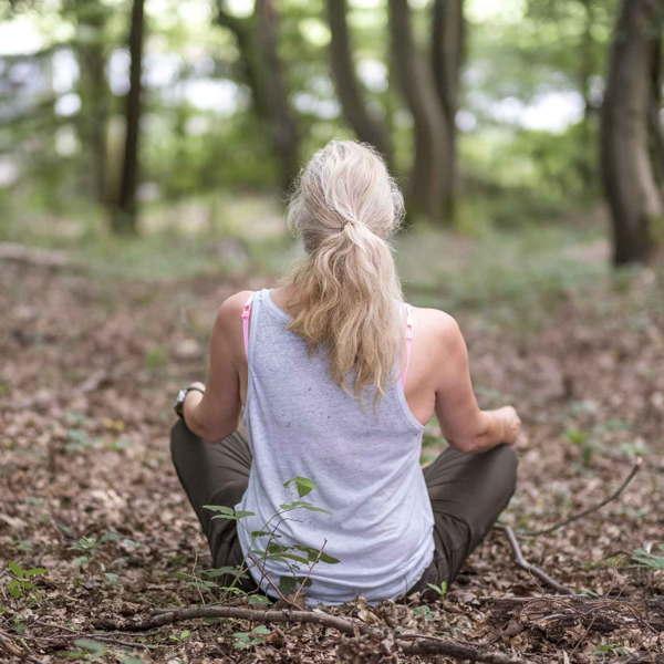 Eine Frau genießt das Waldbaden im Hanfbachtal.