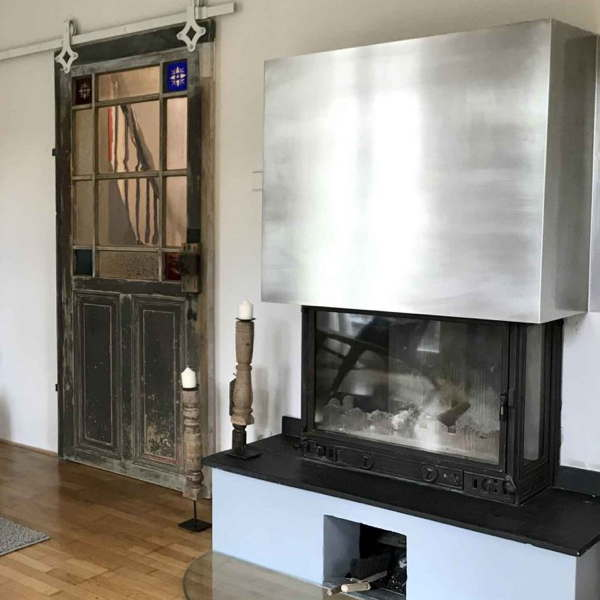 Die alte bleiverglaste Eingangstür im Haus und ein moderner offener Kamin aus Edelstahl.