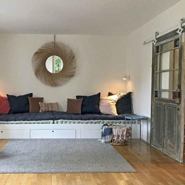 Wohnzimmer im Ferienhaus mit gemütlicher Sitzecke und shabby-chic Eingangstür.