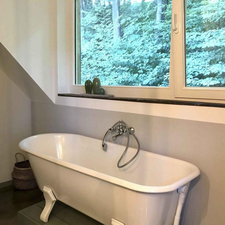 Eine Badewanne mit Füßen steht auf einem Podest direkt unter dem Fenster im Dachgeschoss.