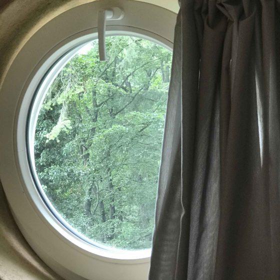 Ein rundes Fenster im Giebel des Hauses.