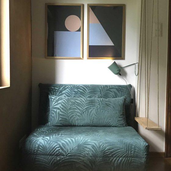 Ein dunkelgrünes Sofa unter zwei sehr modernen Bildern.
