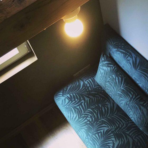 Blick von oben auf einen grünblauen Sessel.