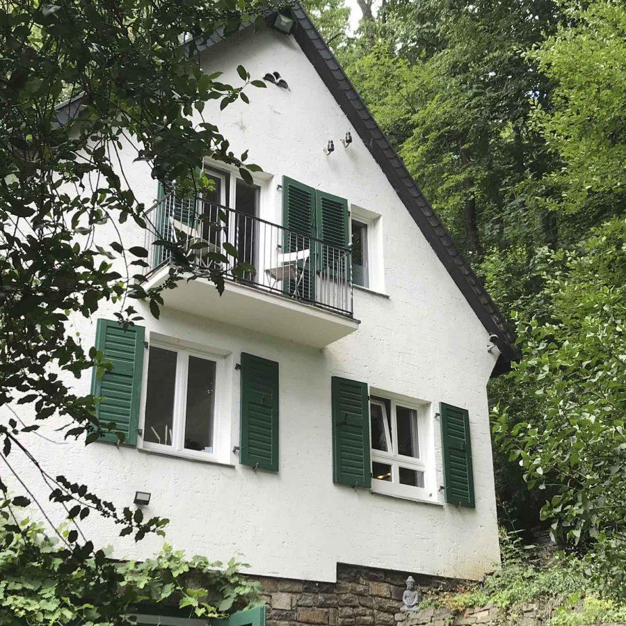 Die Aussenfassade des Ferienhauses mit dunkelgrünen Schlagläden.