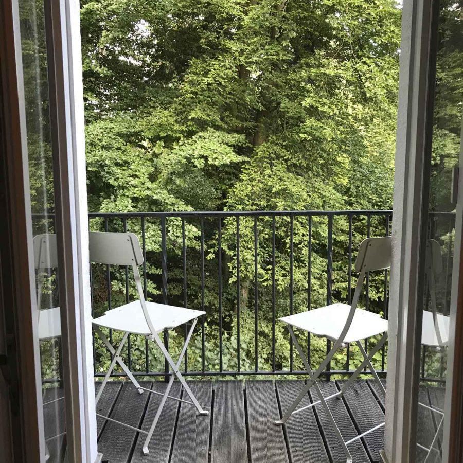 Ein kleiner Balkon im ersten Stock mit Blick auf schönes alte Bäume.