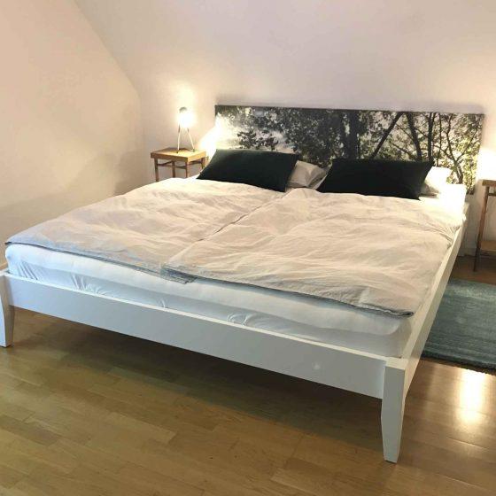 Ein bequemes großes Doppelbett in einem Zimmer des Ferienhauses.