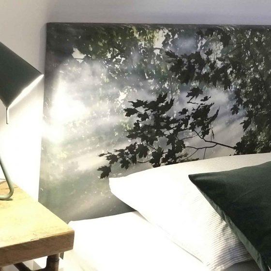 Ein Waldmotiv befindet sich am Kopfende des einen Bettes.