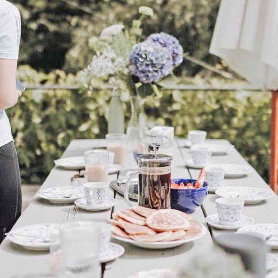 Der Große Holztisch auf der Terrasse des Hanfbachhaus lädt zum Kaffeetrinken ein.