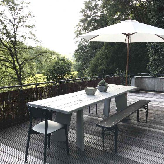 Die große Terrasse mit Holztisch und wunderbarem Blick in das Hanfbachtal im Westerwald.