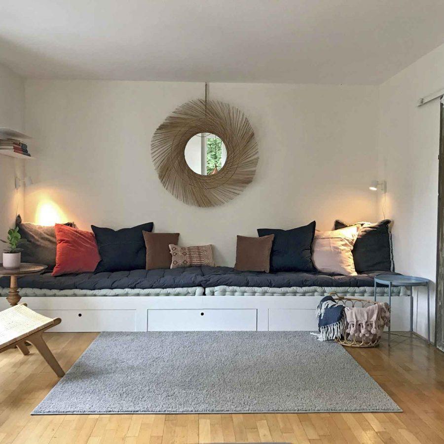 Das sehr breite gemütliche Sofa im Wohnzimmer ist mit Futons belegt.